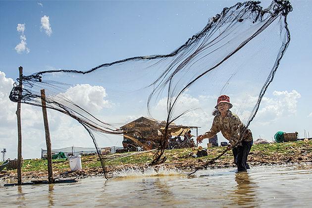Cast fishing net on Tonle Sap Lake - 25 Days in Indochina