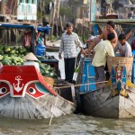 Small boats full of vegetable and fruit making purchase together in Cai Rang Floating Market