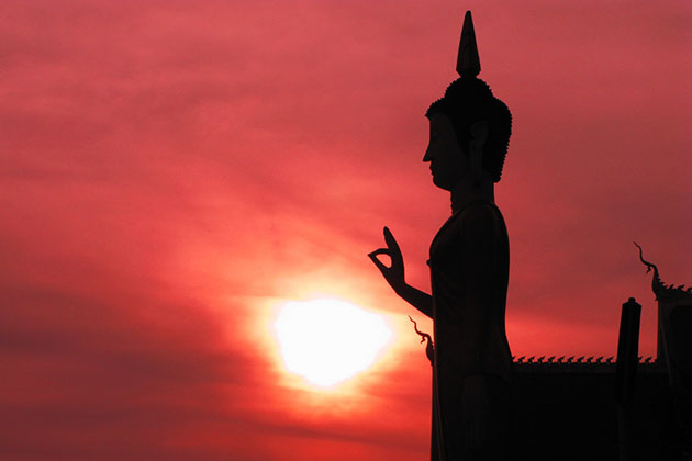 Admire the sunset at That Luang
