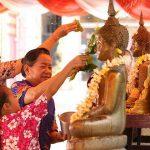 The grandma guide her child how to bath the Buddha in Bunpimay, Laos