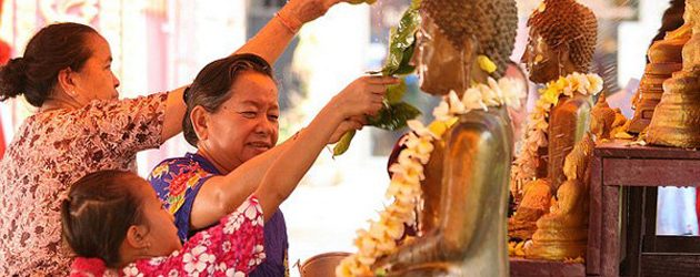 The grandma guide her child how to bath the Buddha in Bunpimay, Laos