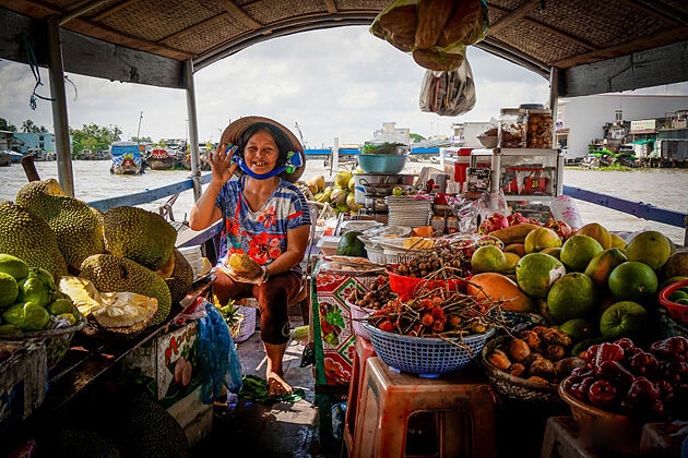 Woman sells fruits on boats in Cai Be floating market
