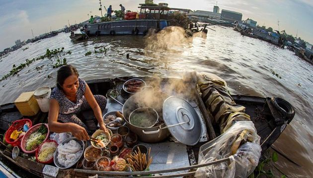 A Woman Sells Foods on Boat in Cai Rang Floating Market