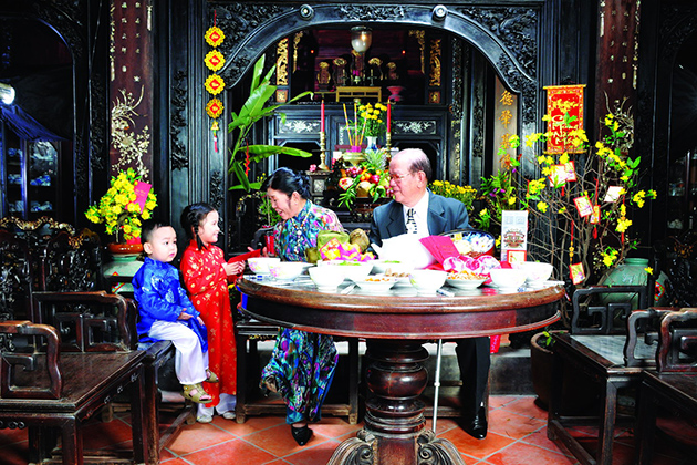 The grand parent and grand children in the meal during Tet Holiday